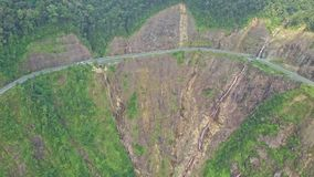Drone approaches mountain highway curve on steep cliff stock video