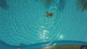 Drone approaches to girl swimming in pool rippling water stock video