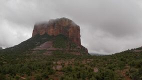 Drone approaching massive red rock in Sedona during cloudy day