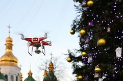 Drone on the background of the Christmas tree. Quadcopter shoots New Year`s video.  Stock Photo