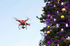 Drone on the background of the Christmas tree. Quadcopter shoots New Year`s video.  Royalty Free Stock Image