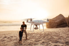 Drone being operated by father and son on beach. Drone being operated by father and son at the sea shore. Father and son on summer vacation flying drone on beach stock photos