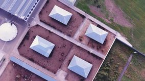 Drone camera catches roofs of modern fenced farm with square animal corral. Camera catches several roofs of buildings belonged to modern, clean, fenced animal stock footage