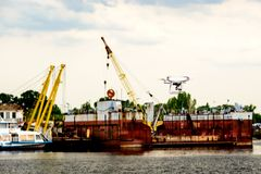 Drone with camera flying on container cargo ship at shipping port. double exposure stock image