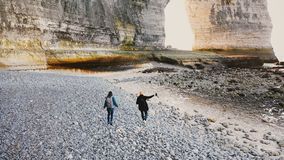 Drone camera follows happy tourist man and woman walking along beautiful big pebble beach to majestic rocks in Normandy. stock footage