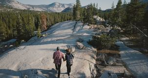 Drone camera follows young romantic couple hiking together along amazing white rock at Yosemite national park forest. Concept of wanderlust, perfect stock footage