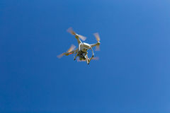Drone with camera hovering in blue sky. Royalty Free Stock Images