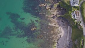 Drone camera looking down at Cornish rocks and coastline. UAV Drone flying over the Cornish fishing village of Mevagissey on a very warm calm day stock video