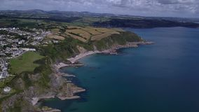Drone camera looking down at Cornish rocks and coastline. UAV Drone flying over the Cornish fishing village of Mevagissey on a very warm calm day stock video footage