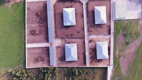 Drone camera shoots roofs of modern fenced farm with square animal corrals. Camera shoots several roofs of buildings belonged to modern, clean, fenced animal stock video footage