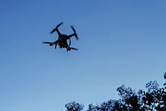 Drone with camera silhouetted Stock Images