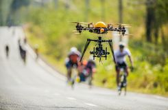 Drone camera up in the air. A shot drone camera up in the air take a sport movie on blur background of cycling bicycle on the street at countryside of Thailand royalty free stock photography