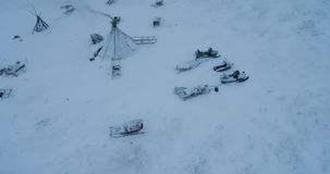 Drone capturing video of a yurts in the middle of field in Arctic , reindeers and sleigh are beside the yurts. Drone capturing video of a yurts in the middle of stock footage