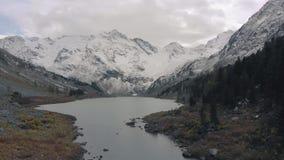 Drone cinemático sobrevoando um lago e a floresta nas montanhas Linha da costa de um lago montanhoso com barcos e florestas filme