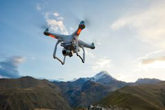 Drone copter flying with digital camera in mountains Stock Photo