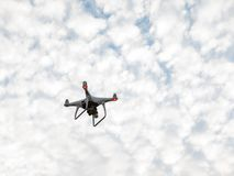 Flying drone with digital camera. Drone copter is flying with digital camera on sky background Royalty Free Stock Image
