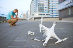 Drone crash. Fallen damaged quadrocopter in city. Drone crash. Fallen damaged flying quadrocopter lying on the ground stock photos