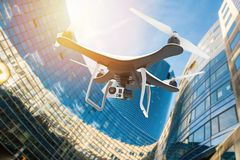 Drone with digital camera flying in a modern city at sunset Royalty Free Stock Photo
