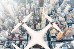 Drone with digital camera flying over a big city in sunlight Royalty Free Stock Photo