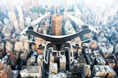 Drone with digital camera flying over a modern big city in the sunlight Stock Photos