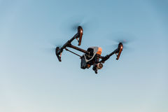 Drone with digital camera flying in sky over field on sunset Royalty Free Stock Images