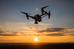 drone with digital camera flying in sky over field on sunset Stock Image