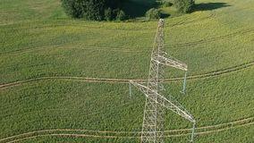 Drone fall away landing near high electricity tower on field, aerial stock video