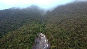 Drone Flies above Fast River and Mountain in Background. Drone flies above fast river in tropical woods and mountain covered with deep fog in background stock video footage