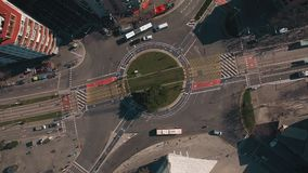 Drone flies above industrial district in town. Top view, aerial spinning shot of urban roundabout way busy with traffic, tram road, bicycle lane and various stock footage