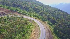 Drone flies above mountain road curve among woods stock video