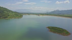 Drone flies above lake with island against hills cloudy sky. Drone flies above pictorial lake and small green island against majestic hilly landscape and blue