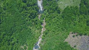 Drone flies along narrow river in green canyon of highland. Drone flies along narrow river with waterfall in canyon among boundless hilly lands covered tropical stock video