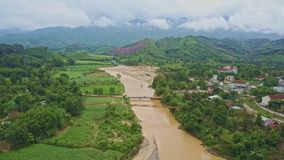 Drone Flies along River Running among Tropical Landscape. Drone flies along long quiet brown river running between green banks of tropical landscape against stock video footage