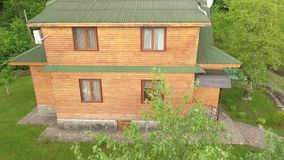 Wooden Apartments on the Territory of a Tourist Complex. The drone flies away from wooden two-storeyed apartments in the territory of a tourist complex. Trees stock video