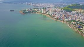 Drone Flies from Modern Resort City on Azure Ocean Shore. Drone flies from big modern resort city with skyscrapers over azure ocean shore against blur distant stock footage