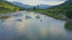 Drone flies over clear river with sky reflection against highlands. Drone flies over clear shallow river with sky reflection against tropical highlands in stock video