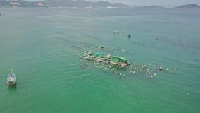 Drone flies over fishing farm in ocean against peninsula stock video footage