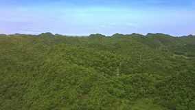 Drone Flies over Highland Covered with Jungle under Blue Sky. Drone flies over beautiful hilly island covered with boundless green jungle under clear blue sky stock video
