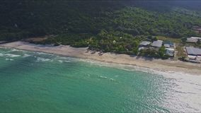 Drone Flies over Jungle Beach with Ocean Surf against Hills stock video