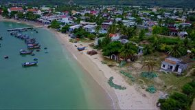 Drone flies over Quiet Bay with piers boats and nice town. Drone flies over quiet bay with piers bright fishing boats along sand beach and small nice town in stock video footage