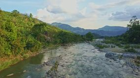 Drone flies over rocky river running against green hills sky stock video footage