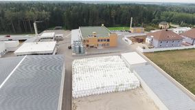 Drone flies over roofs of modern clean fenced farm with pile of round bales. Drone camera demonstrates several roofs of buildings belonged to modern clean stock video