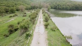 Drone flies on a rural road that runs along a lake. Fly over a natural park in Sicily, forest lake landscape, 4k resolution stock video footage