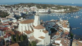 Aerial shot of ancient church in Cadaques town. Drone flight around church of St. Mary in coastal town of Cadaques on background of beautiful blue bay with stock video