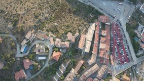 Drone flight from bay of Cadaques to mountain road. Top view of blue bay, quay, white houses with tiled roofs, narrow streets, church of medieval coastal town stock footage