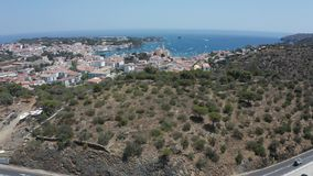 Drone flight from Cadaques over mountain hills. Aerial view of hills overgrown with trees and shrubs, winding road to Cadaques on background of Cap de Creus stock footage