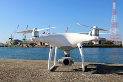 Drone before the flight on concrete blocks. KAGAWA, JAPAN - MAY 28, 2017: White drone Dji Phantom4Pro stay on concrete blocks for protection of port and ready to Stock Photography
