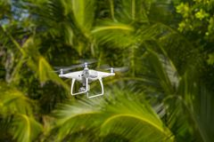 Drone in flight, green trees in the background, selective focus on the drone.  stock photos