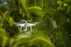 Drone in flight, green trees in the background, selective focus on the drone.  stock image