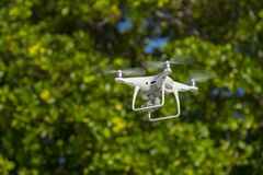 Drone in flight, green trees in the background, selective focus on the drone.  royalty free stock photos